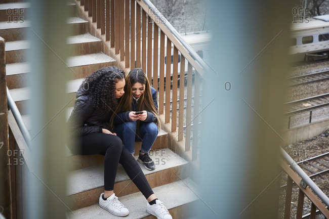 Teenage girl showing mobile phone to female friend while sitting on steps
