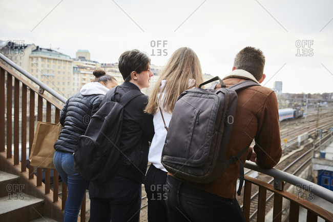Teenage male and female friends leaning on railing of staircase in city