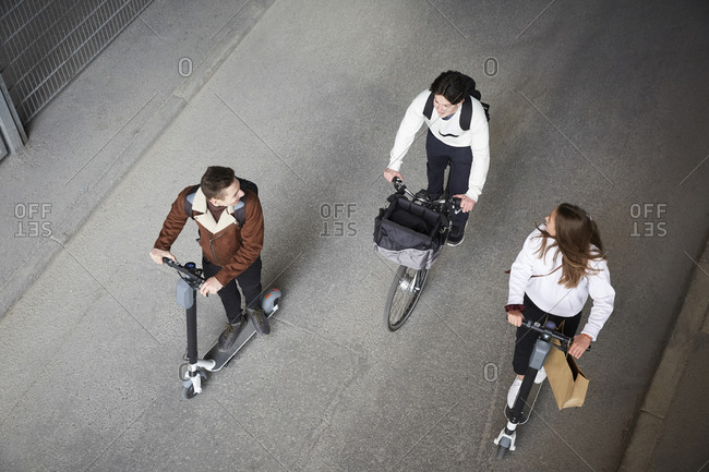 High angle view of male and female friends riding electric push scooters and bicycle on road in city
