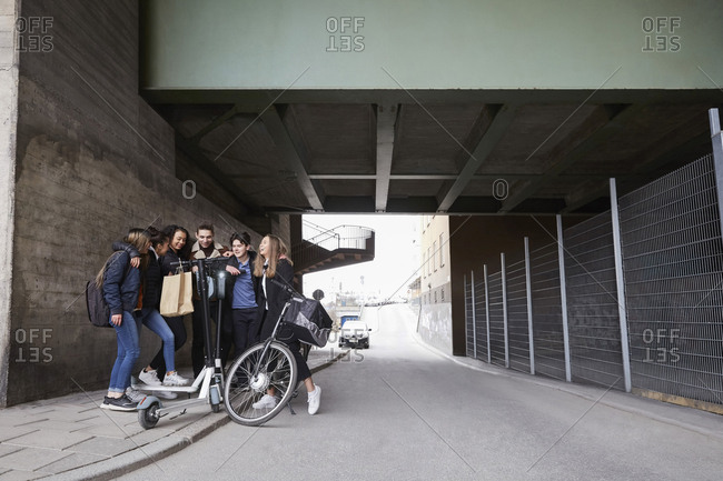 Teenage male and female friends with push scooters and bicycle on sidewalk below bridge