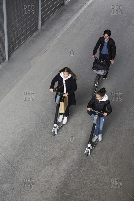 High angle view of male and female friends riding electric push scooters and bicycle on street in city