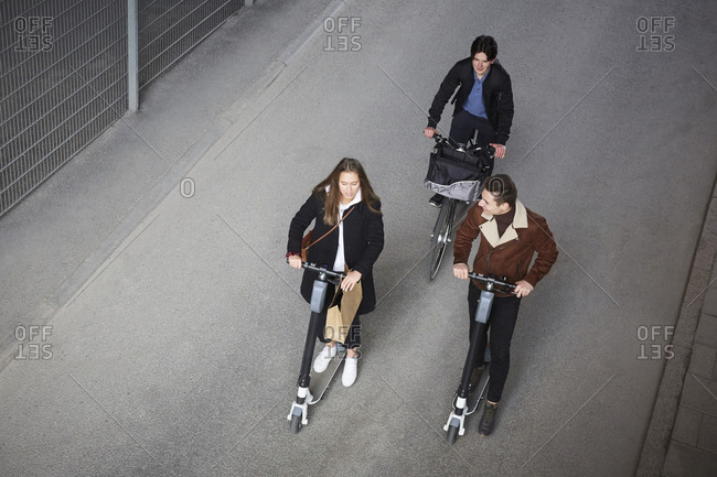 High angle view of teenage friends riding electric push scooters and bicycle on street in city