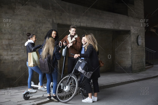 Smiling teenage male and female friends with push scooters and bicycle on footpath