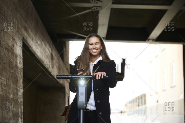 Portrait of smiling teenage girl with electric push scooter holding mobile phone below bridge