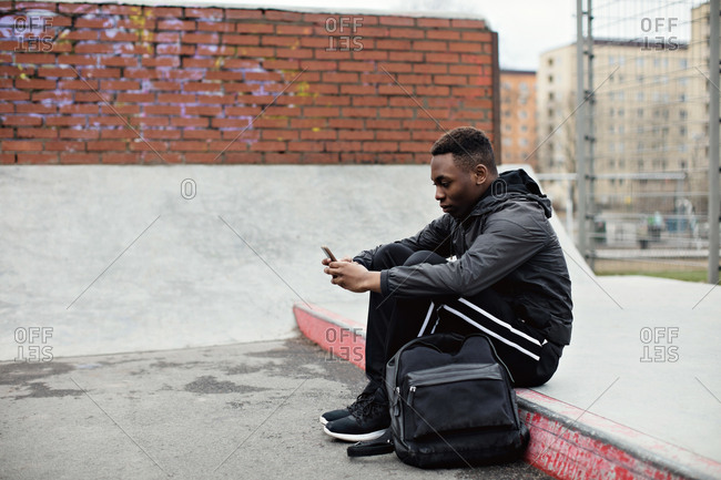 Side view of teenage boy using smart phone while sitting in city during winter