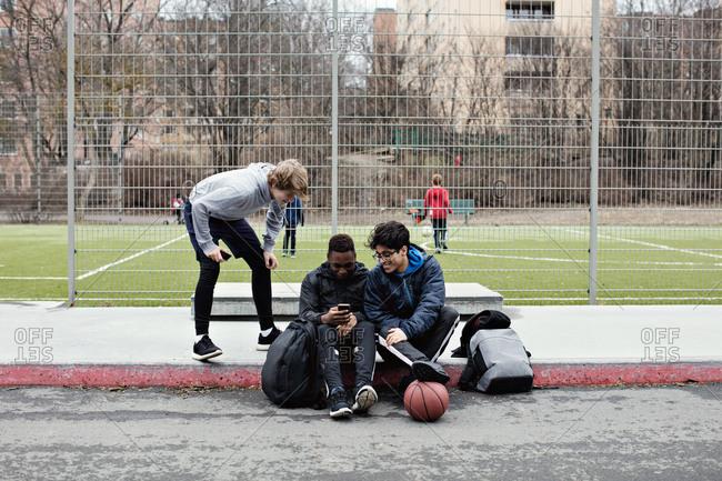 Teenage boy looking at friends using social media on sidewalk against soccer field in city