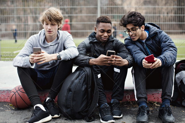 Social media addicted friends using mobile phones while sitting on sidewalk after basketball practice in city