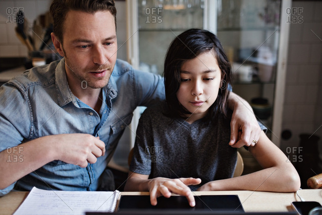 Son using laptop by father while doing homework at home