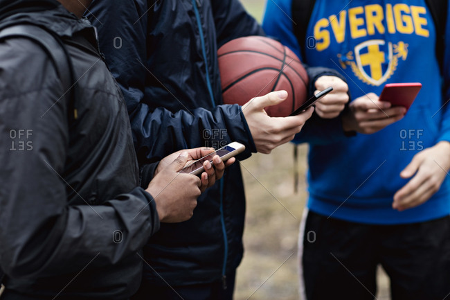 Midsection of phone addicted friends wearing warm clothing while standing on basketball court