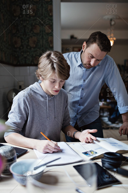 Father looking at son doing homework on table