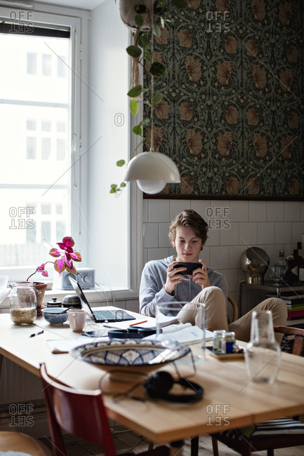 Teenage boy using mobile phone while studying at home