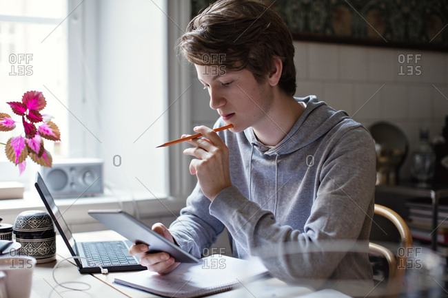 Serious teenage boy using digital tablet while doing homework on table