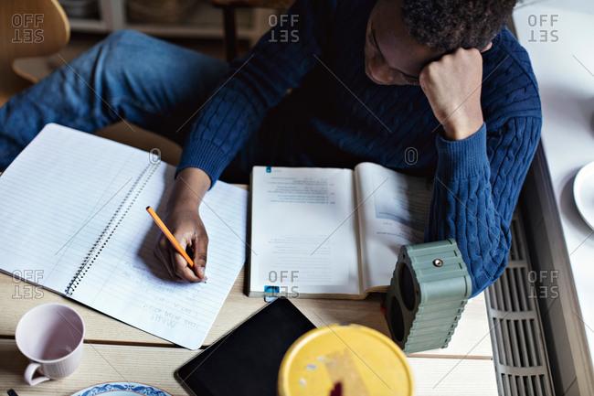 High angle view of teenage boy writing on book while doing homework