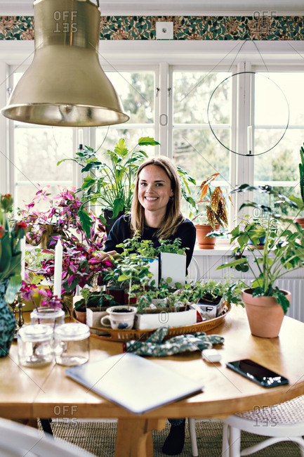 Portrait of smiling woman gardening at table against window in room