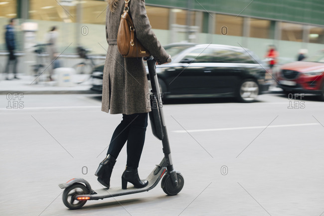 Low section of businesswoman riding electric push scooter on street in city