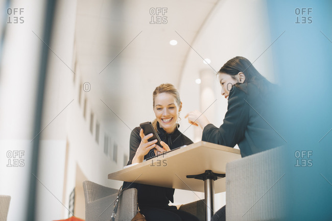 Low angle view of smiling businesswoman sharing smart phone with female colleague at table in office