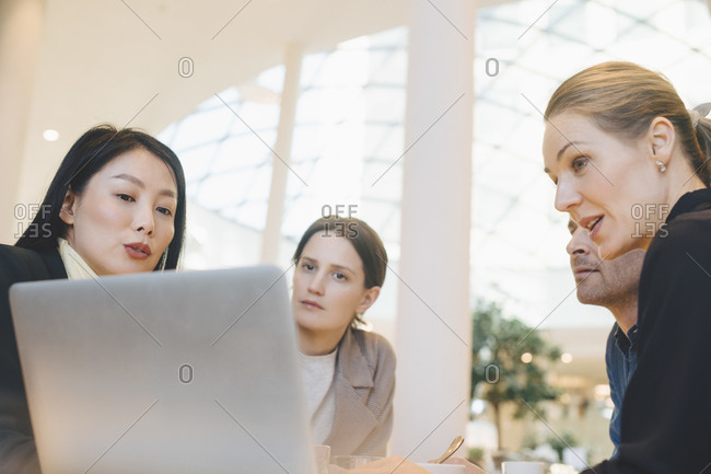 Confident team of business colleagues discussing over laptop at cafeteria in office