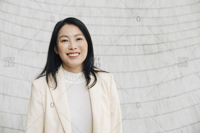 Portrait of smiling businesswoman in blazer standing against wall at office