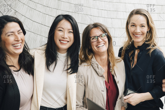 Portrait of happy multi-ethnic female business professionals standing against wall