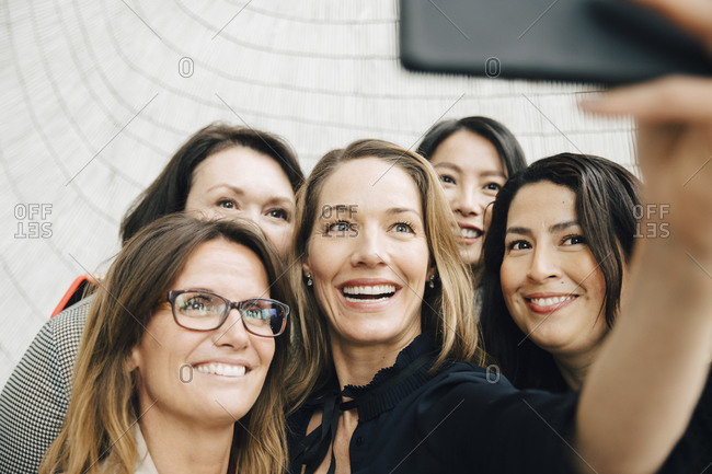 Smiling businesswoman taking selfie with female professionals at office during conference event