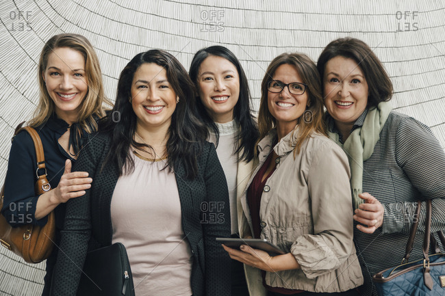 Portrait of smiling multi-ethnic female business professionals standing against wall at workplace