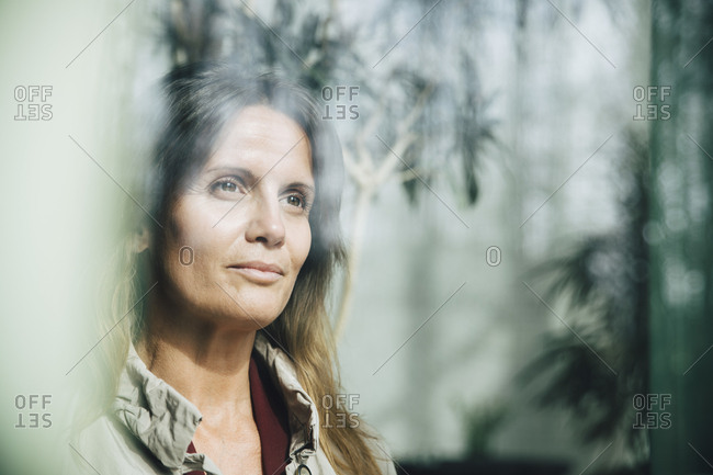 Thoughtful mature businesswoman looking through window at office