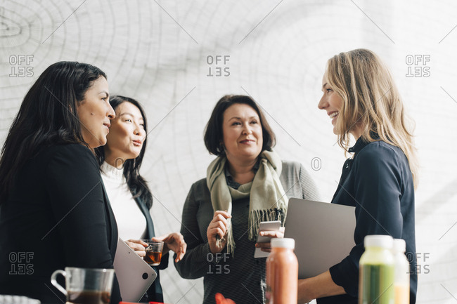 Female colleagues listening to businesswoman in meeting at conference event