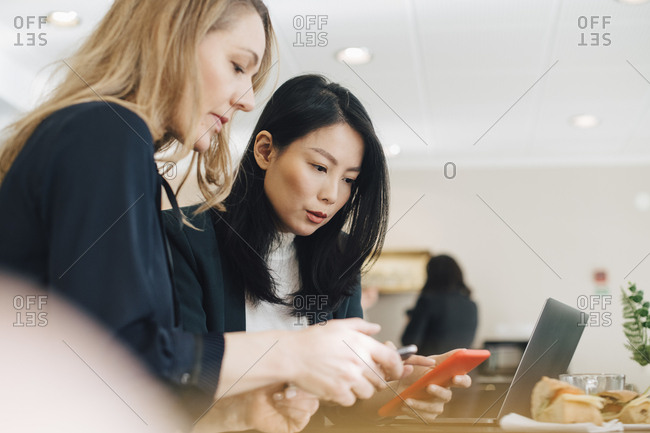 Female colleagues using smart phones while sitting at conference table in board room