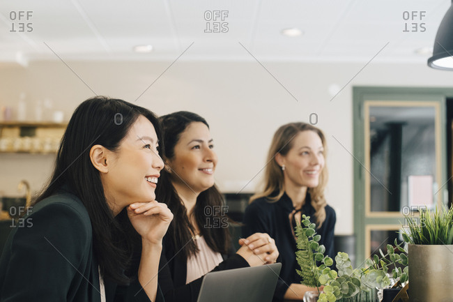 Smiling businesswomen sitting at conference table in meeting