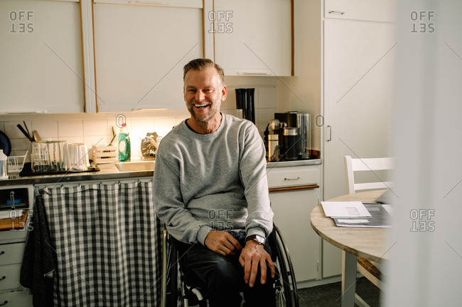 Cheerful mature man sitting on wheelchair in kitchen at home