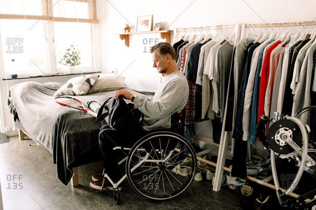 Side view of disabled mature man packing tennis racket in bag while sitting on wheelchair at home