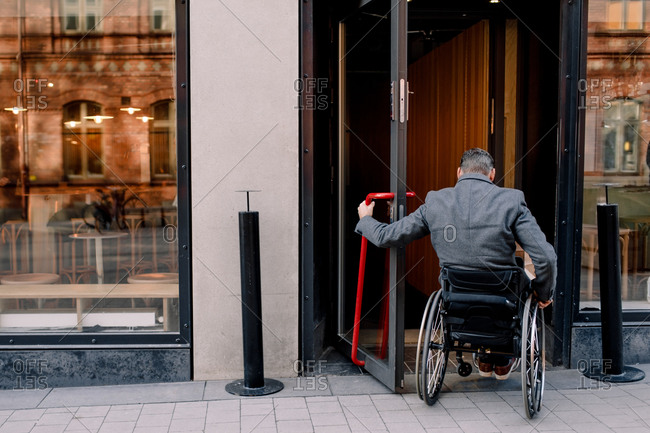 Rear view of disabled mature man sitting on wheelchair while entering in store