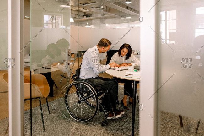Serious female manager and disabled businessman working in board room