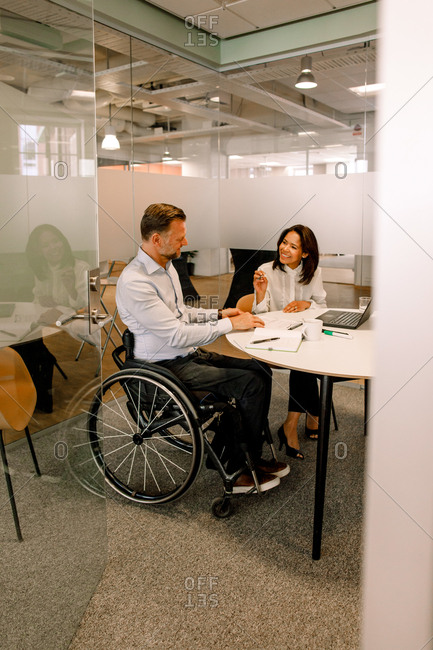Smiling businesswoman discussing sales plans with disabled manager while sitting in board room