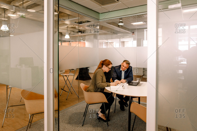 Sales executives discussing over business plans while sitting at work place seen through doorway