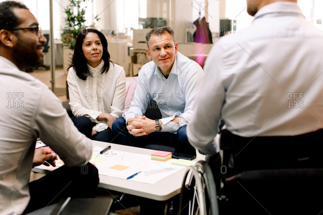 Business colleagues looking at disabled sales manager during meeting in office