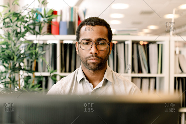 Male business professional wearing eyeglasses while working in office