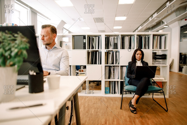 Serious businessman working at office desk while female colleague using laptop in background