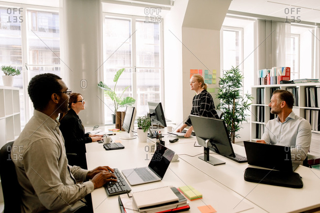 Business colleagues planning sales strategies at desk in office