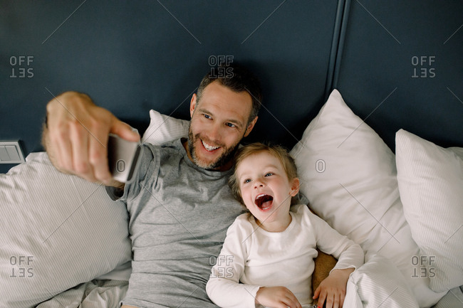 High angle view of father taking selfie with daughter on bed in hotel