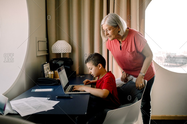 Grandmother looking at grandson using laptop while sitting by table in hotel room