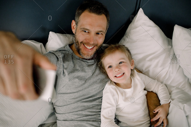 High angle view of happy father taking selfie with smiling daughter on bed in hotel