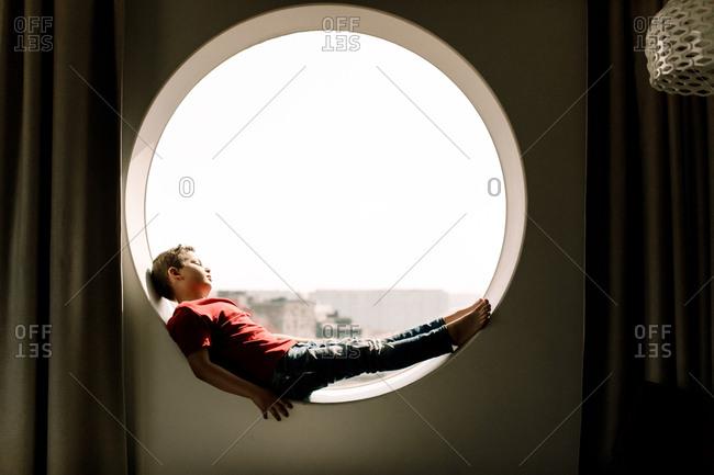 Full length of boy lying on circular window