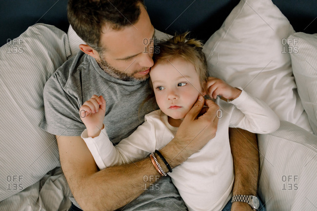 Directly above shot of father with daughter lying in bed