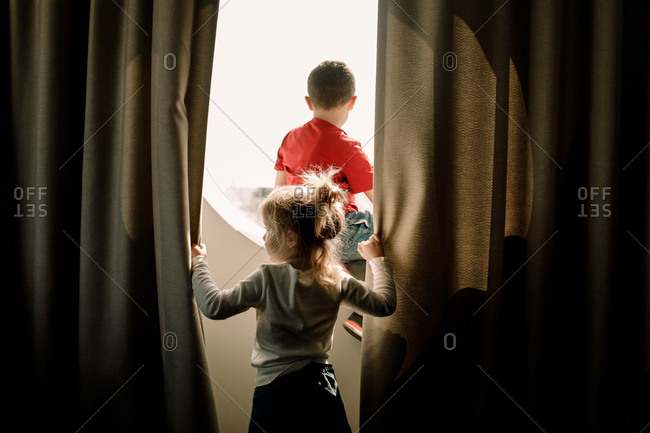 Rear view of girl holding curtain while brother sitting on window in hotel room