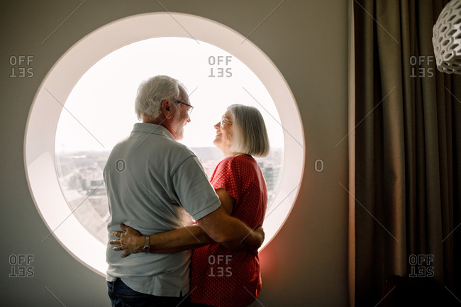 Senior couple embracing while standing by window in hotel room