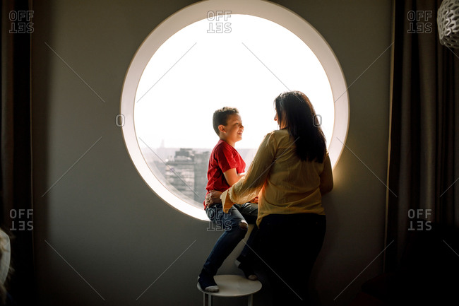 Smiling son looking at Mother while sitting on window in hotel room