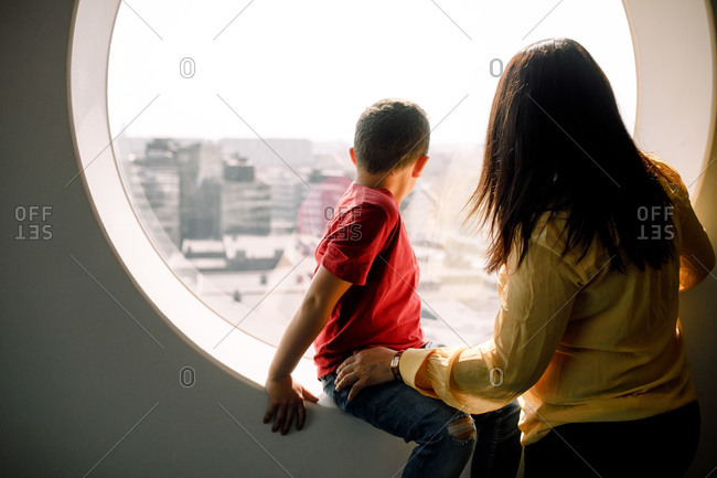 Mother and son looking through window from hotel room
