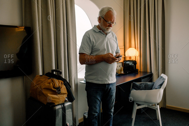 Senior man using smart phone while standing in hotel room
