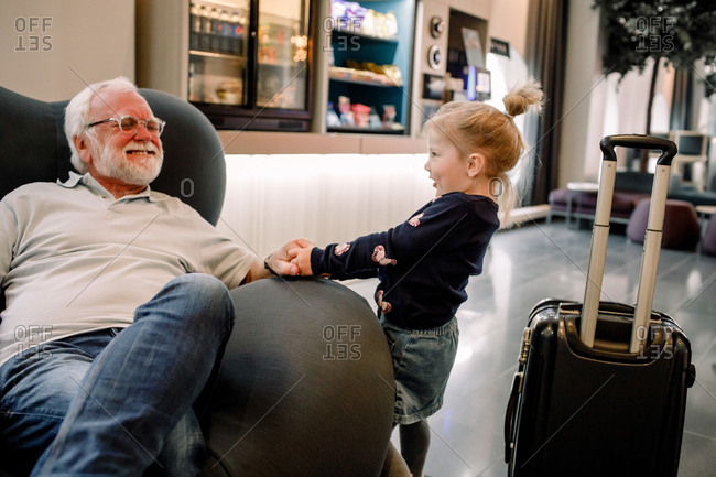 Side view of girl pulling grandfather sitting on armchair in hotel lobby
